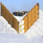 Trains Plowing Through Snowy Railway Tracks